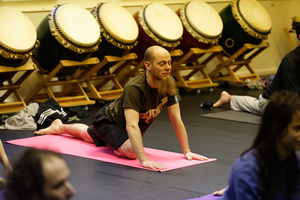 A delegate practicing yoga during an early morning session at the European Taiko Conference.
